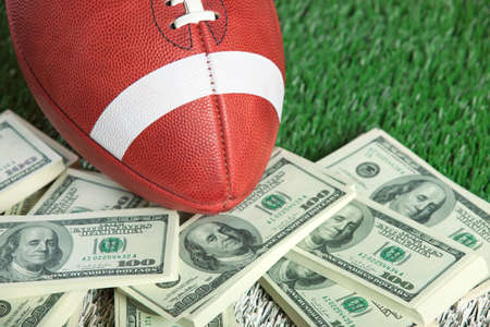american currency: A college style football sits with a pile of money on a green field