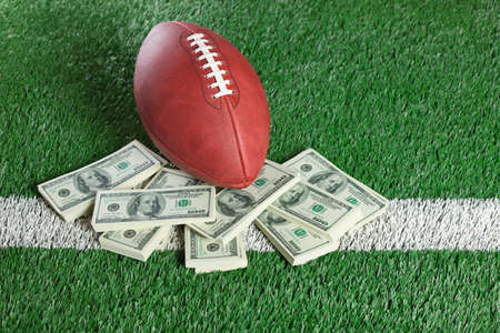 american currency: An NFL football sits with a pile of money on a green field Stock Photo