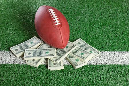Ein NFL Football sitzt mit einem Haufen Geld auf einem grünen Feld Standard-Bild - 23208809