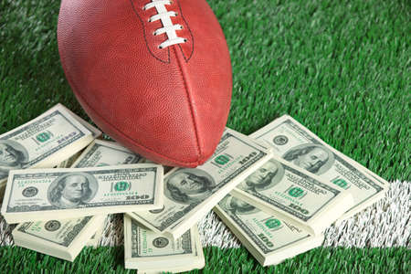 An NFL football sits with a pile of money on a green field  Stock Photo