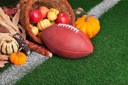 A football with a cornucopia on a grass field with white stripe  Stock Photo