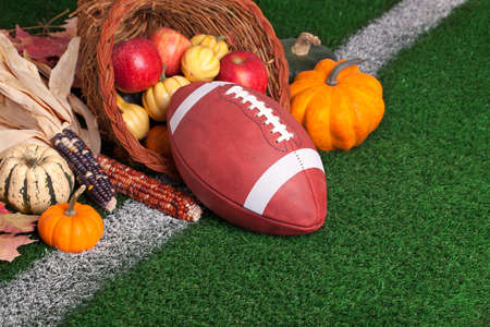 A college style football with a cornucopia on a grass field with white stripe