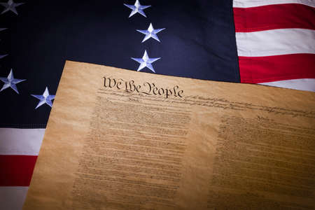 colonies: A United States flag with thirteen stars and the Constitution laying on it