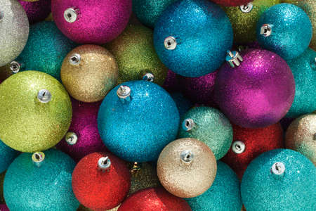 A group of sparkly Christmas baubles of different colors