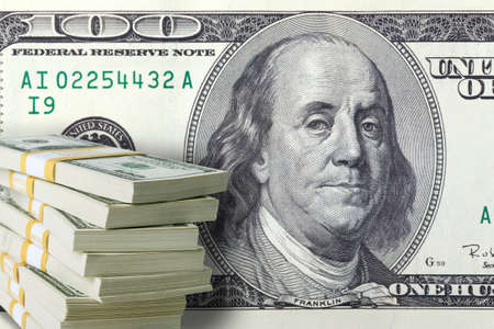 ben franklin: A stack of one hundred dollar bills in front of a large one Stock Photo