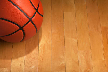 Basketball with spot lighting on a wood gym floor
