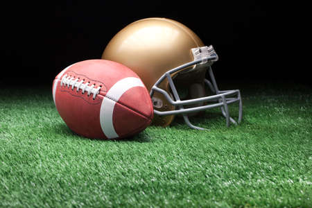 College style football and helmet on grass field against dark