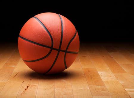 cancha de basquetbol: Una pelota de baloncesto con un fondo oscuro en un piso del gimnasio de madera