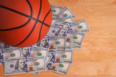 A basketball on a pile of one hundred dollar bills viewed from above photo