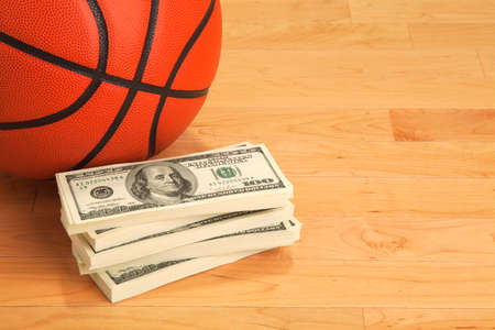 Basketball and stack of one hundred dollar bills on wooden court floor photo