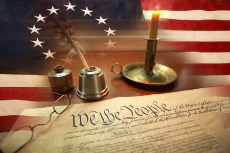 US Constitution with quill pen, ink, glasses, candle and flag with thirteen stars 免版税图像