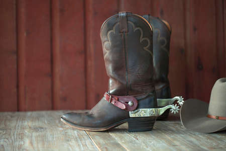 Cowboy boots with spurs and a hat on an old wood  Stock Photo