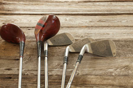 Old golf clubs on rough wooden surface