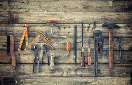 Old antique tools viewed from above on rough wood surface photo