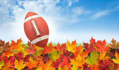 College style football with fall leaves on grass, blue sky and clouds