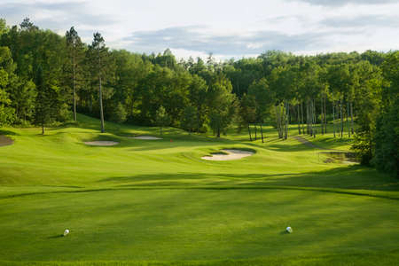 golf tee: A golf green with bunkers with backdrop of trees in afternoon sunlight viewed from the tee box