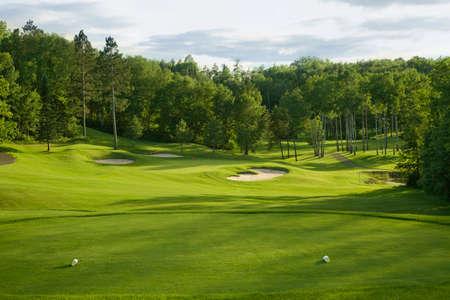 Een golf green met bunkers met de achtergrond van de bomen in de middag zon gezien vanaf de tee box