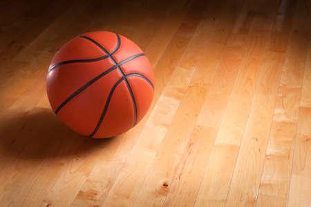 cancha de basquetbol: El baloncesto de color naranja se sienta en un piso de madera dura de tenis con iluminación puntual y el fondo que va de la oscuridad a la luz. Foto de archivo