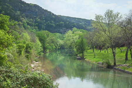 The Guadalupe River below cliffs of the Texas Hill Country during Spring Stock Photo