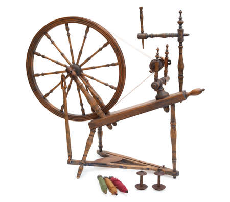 An antique wooden spinning wheel with yarn and bobbins isolated on a white background 免版税图像