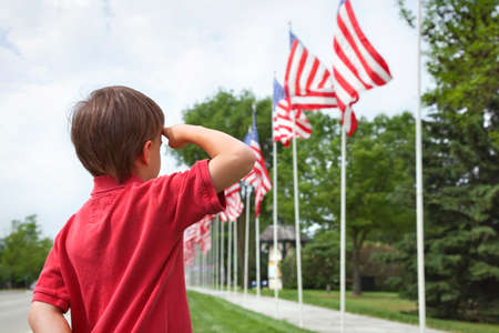 A young boy salutes the flags of a Memorial Day display along a small town street Фото со стока