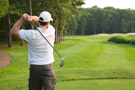 par: Young male golfer in white shirt and white hat tees off with an iron on a par three