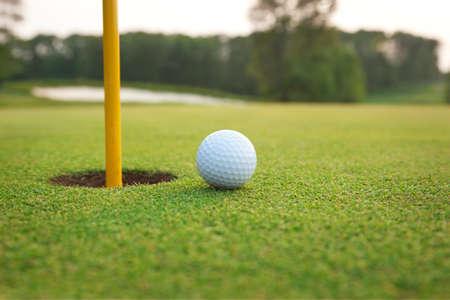 pelota de golf: Cierre de la pelota de golf en una zona verde cerca del agujero con el pasador y el fondo desenfocado Foto de archivo