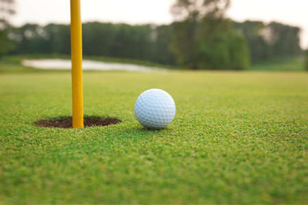 Close up of golf ball on a green near the hole with pin and defocused background