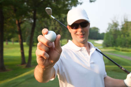 Selective focus view of a smiling young Caucasian male golfer holding a ball out in front of him while also holding a club
