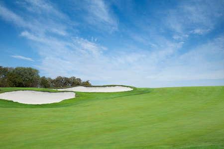 明るい青い空の雲の下のバンカーとグリーン ゴルフ フェアウェイ 写真素材