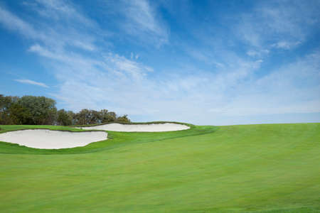 A green golf fairway with sand traps below a bright blue sky with clouds