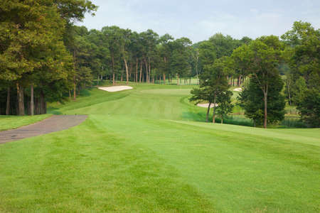 green: A tree-lined golf fairway leads to a green guarded by three sand traps