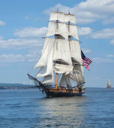 A tall ship known as a brigantine sails on blue water with an American flag flying Stock Photo