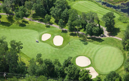 of course: Aerial view of a golf course fairway and green with sand traps, trees and golfers Stock Photo