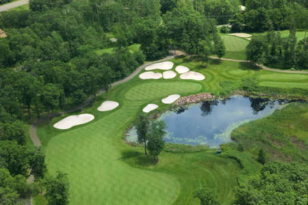 ponds: Aerial view of golf course fairway and green with sand traps, pond and trees