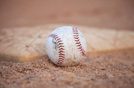 infield: Selective focus low angle view of a grungy baseball and base in the infield Stock Photo