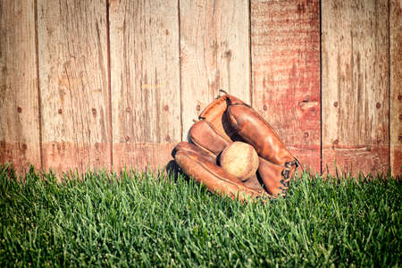 mitt: Old leather baseball mitt and ball on grass field against a rough wooden fence