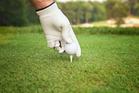 golf glove: A selective focus, low angle view of a golfers gloved hand placing a ball on a tee