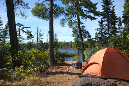 A campsite with an orange tent and cook stove overlook a Boundary Waters lake in northern Minnesota 免版税图像