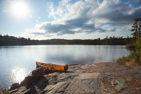 An orange canoe on a rocky shore of a Boundary Waters lake in northern Minnesota near sundown