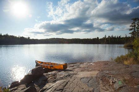 An orange canoe on a rocky shore of a Boundary Waters lake in northern Minnesota near sundown