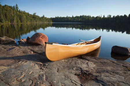 A yellow canoe rests on a rocky shore of a calm blue lake in the Boundary Waters of Minnesota