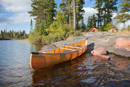A campsite with a yellow canoe on a rocky shore of a Boundary Waters lake in Minnesota 免版税图像 - 45431539