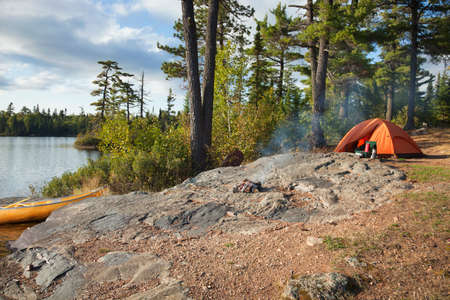 Campsite with orange tent and canoe on a lake in the Boundary Waters Canoe Area Wilderness of Minnesota Stock Photo - 45522202