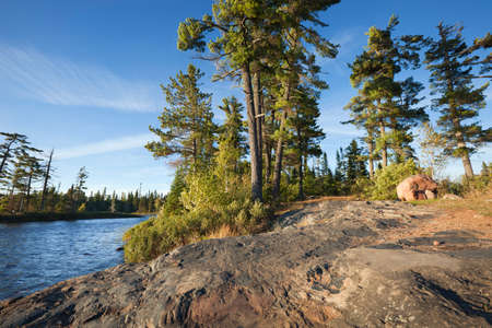 Wide angle afternoon shot of a rocky shore with pine trees on a Boundary Waters Canoe Area Wilderness lake in northern Minnesota