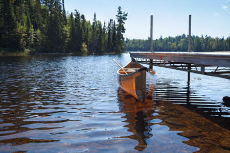 kevlar: A yellow kevlar lightweight canoe tied to a dock on a trout lake in northern Minnesota