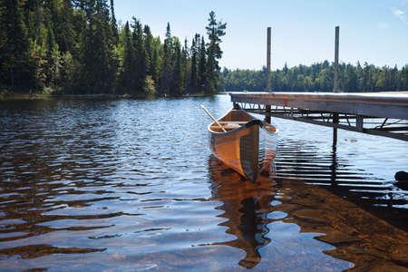 piragua: Una ligera canoa kevlar amarillo atado a un muelle en un lago de truchas en el norte de Minnesota