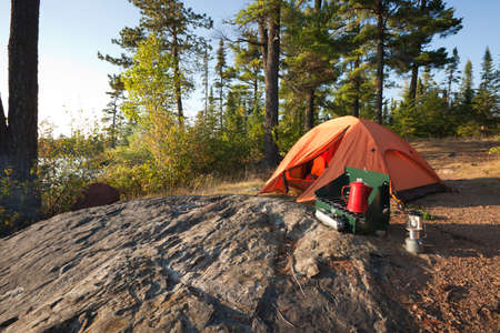 A campsite with an orange tent and cookstove in the north woods of Minnesota