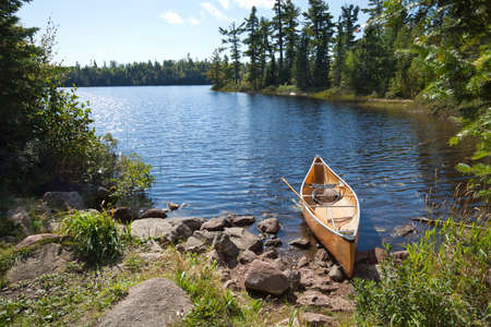 pine trees: A yellow fishermans canoe on a rocky shore of a northern Minnesota lake Stock Photo