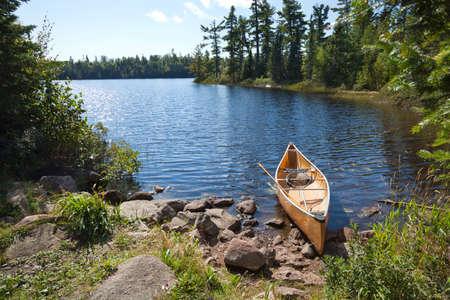 redes pesca: Canoa de un pescador de color amarillo en una orilla rocosa de un lago del norte de Minnesota Foto de archivo